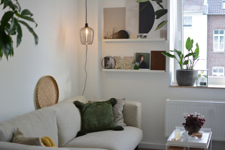 Small living room with cream sofa and green cushions