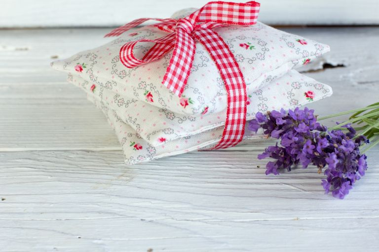 Lavender pillows tied in a bow with a red and white gingham ribbon on the table next to some dried lavender