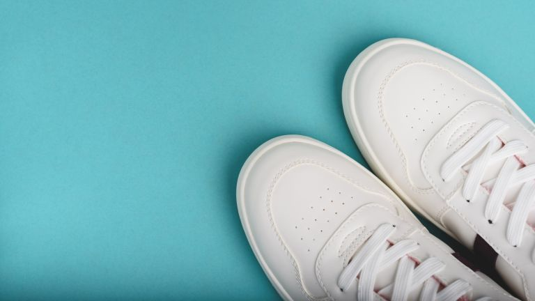 A pair of clean white sneakers pictured against a blue background