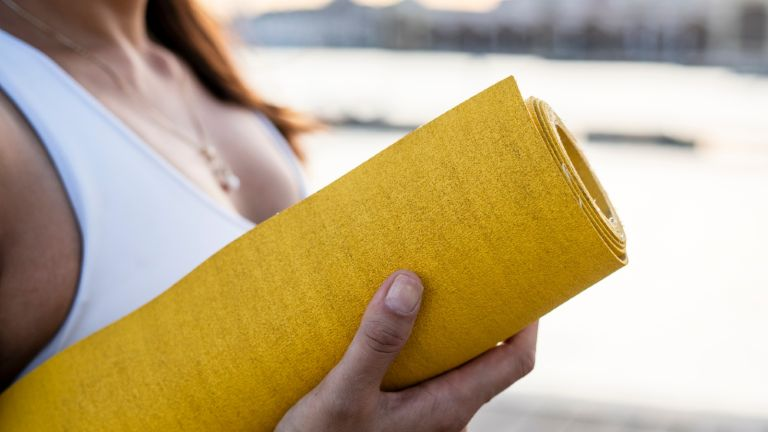 Yogamatters Sticky Yoga Mat VS Yogi Bare Paws Natural Rubber Extreme Grip woman holding yoga mat yellow