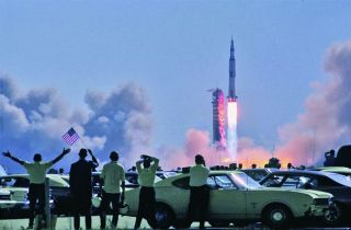 Spectators in a parking lot near the Vehicle Assembly Building wave an American flag as Apollo 11 begins its journey to the moon. The Saturn's automatic engine-shutdown function was inhibited during the first 30 seconds to prevent the vehicle from falling back onto the pad during a launch failure — which was seen as the least preferable option at that stage of the flight.
