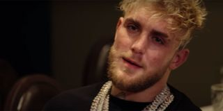 Jake Paul with a black shirt on, rocking some gold chains.