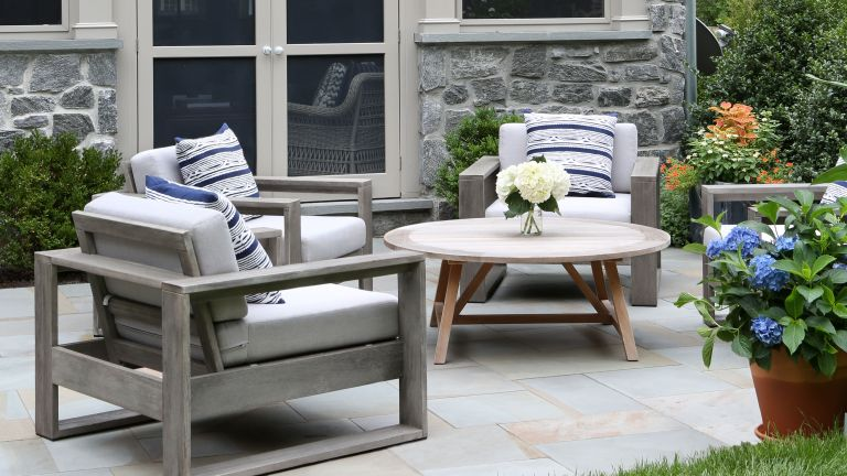 An example of small backyard ideas showing a gray garden building with glass doors behind gray painted patio furniture