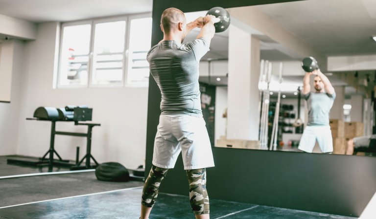 Man wearing a pair of the best workout shorts doing kettlebell swings