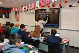 Teacher writes on BenQ flat panel display in front of class