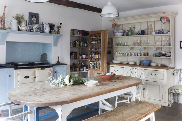 Kitchen with blue and cream units, an aga and wooden kitchen table and chairs