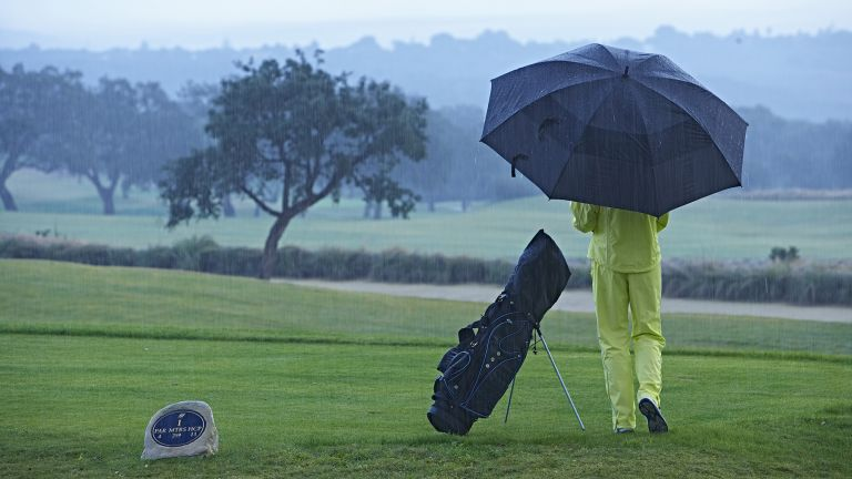 6cfabc8e6c8 Best golfing waterproofs  a man stand dressed in yellow waterproofs stands  on a rainy golf