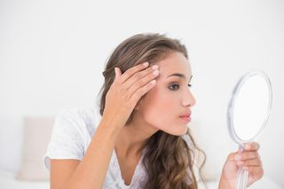A woman looks at her skin in the mirror closely