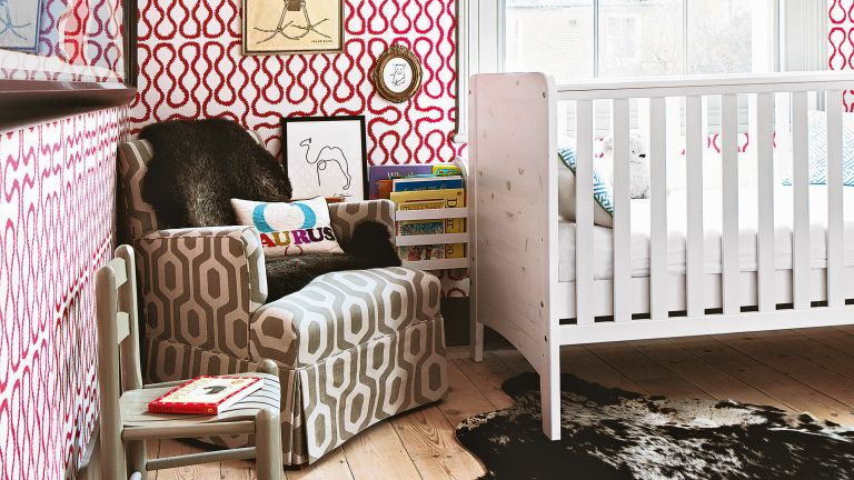 Gender neutral nursery ideas featuring red and white wallpaper, a white painted crib and brown armchair.