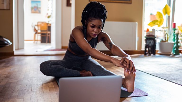 2020 fitness trends: humming yoga Woman at laptop stretching