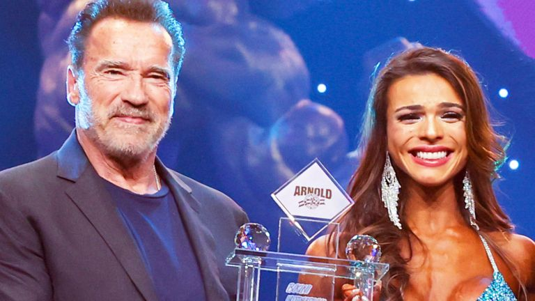 Arnold Schwarzenegger presents female weightlifter Alessia Facchin with a trophy at the Arnold Sports Festival in March 2020