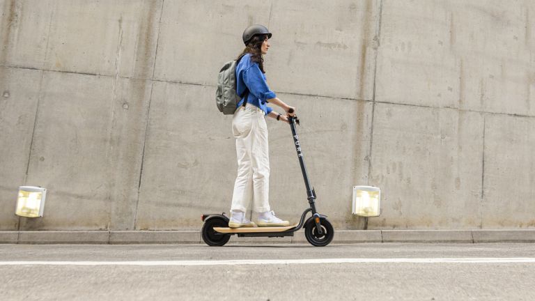 A woman riding the best electric scooter up a hill with a cement wall behind her