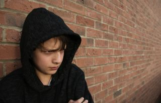 Depressed young teenage boy in a hoodie.