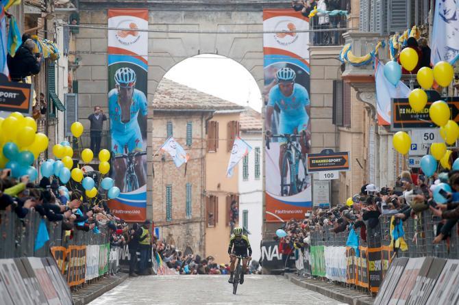 Tirreno-Adriatico stage 5 winner Adam Yates rides into Filottrano under banners honouring Michele Scarponi