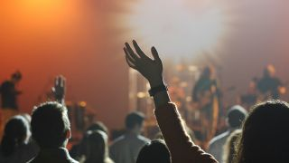 a shot of a woman raising her hand in a crowd at a gig