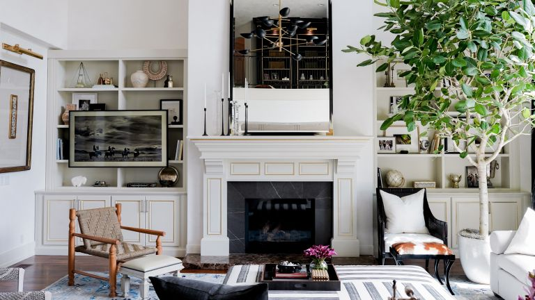 A family room with white walls, white fireplace, large mirror over the mantel, built-in shelves and brown and black armchairs