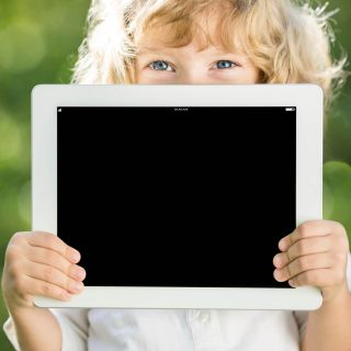 Child holding iPad in front of face
