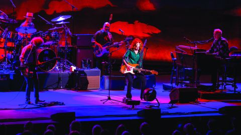 Bonnie Raitt playing guitar onstage with her live band.