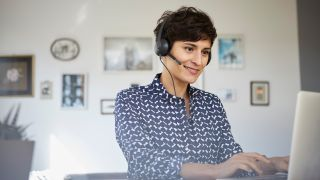 VoIP home phone and VoIP headset used by woman who attends video conference on laptop