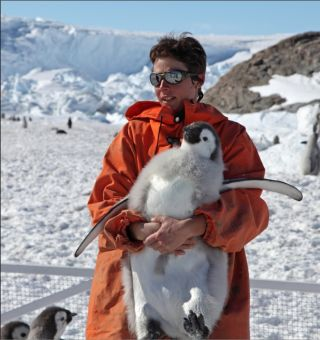 Stephanie Jenouvrier, of Woods Hole Oceanographic Institution, holds an emperor penguin chick in Antarctica.