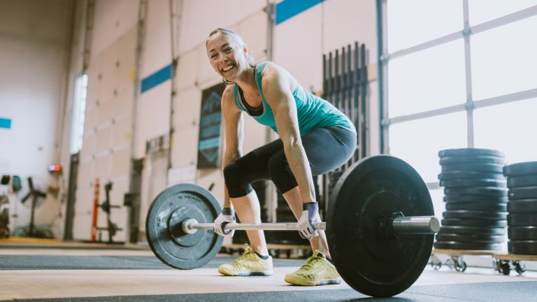 Woman preparing to lift weight as she learns how to deadlift properly with barbells