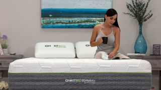 Best GhostBed discounts and sales in September: A woman with long dark hair sits on the GhostBed 3D Matrix Mattress