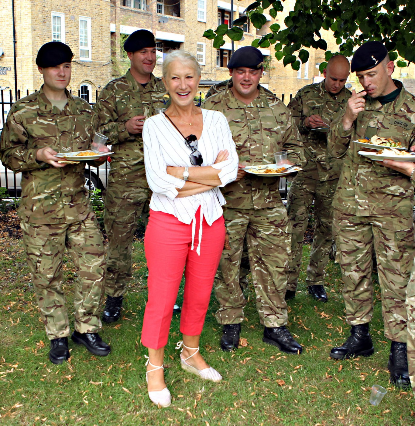 Dame Helen Mirren joins the military parade for armed services at the London 2012 temporary security camp in Wapping