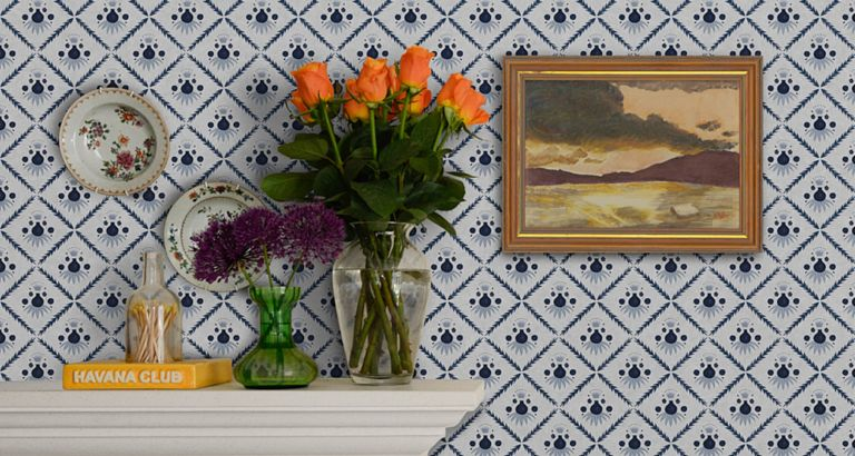 How to wallpaper, with a diamond print blue and white design hung above a fireplace, with plates and a painting mounted on the wall.