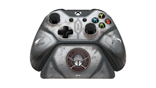 Product render of a gray xbox controller with a charging stand, themed after Mandalorian armor