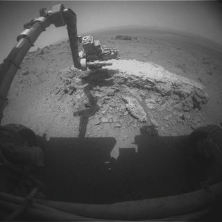 This image shows the Mars rover Opportunity's robotic arm reaching out to the rock Tilsdale 2 at the huge crater Endeavour on the Martian surface on Aug. 23, 2011.