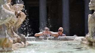 A man cools off in a fountain in Piazza della Rotonda in Rome. A scorching heat wave is fuelling deadly fires across the south of the country.