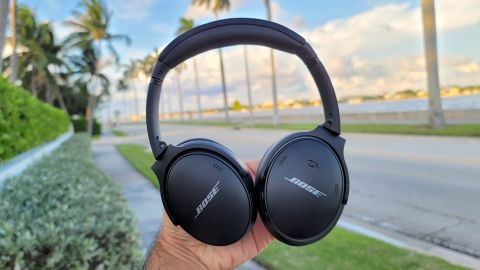 The Bose QuietComfort 45 headphones being held aloft against a backdrop of a coastal street with palm trees