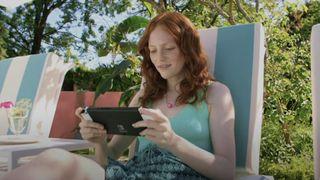 Imagen de prensa de una mujer jugando a la Nintendo Switch OLED en exteriores