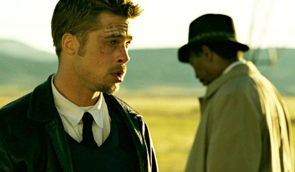 Seven Brad Pitt and Morgan Freeman stand in a field, in a tense situation