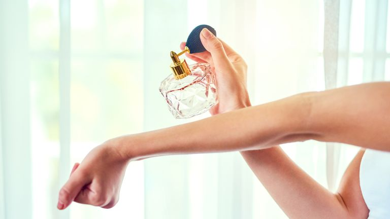 Closeup shot of an unrecognizable woman applying perfume to her wrists