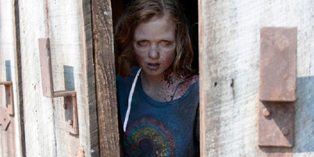Sophia stepping out of the barn in her walker form in The Walking Dead.