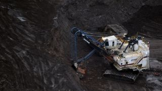 A large excavator loads a truck with oil sands at the Shell Albian mine near the town of Fort McMurray in Alberta Province, Canada on October 23, 2009.