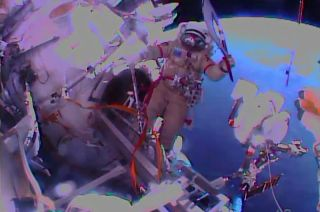 Spacewalker Oleg Kotov is seen with the Olympic torch outside the International Space Station, Nov. 9, 2013.