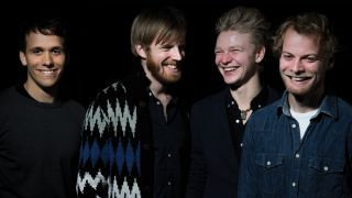 Danish band Vola laughing against a black background