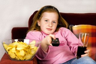 A young girl watches television and eats junk food.