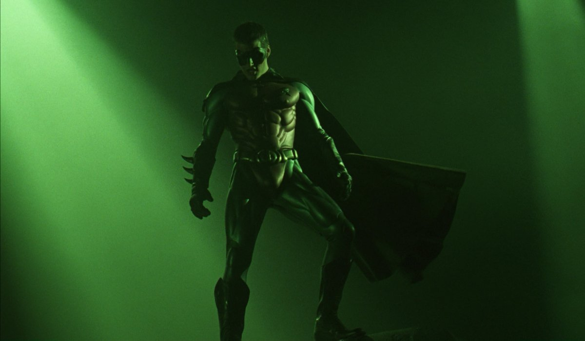 Batman Forever Chris O'Donnell Robin stands on a rock bathed in green light