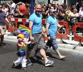 Gay parents march with their child in a Pride parade.