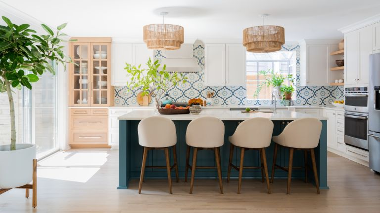 A white kitchen with blue island, taupe bar chairs, white and blue patterned tiles and wooden glass-fronted cabinet