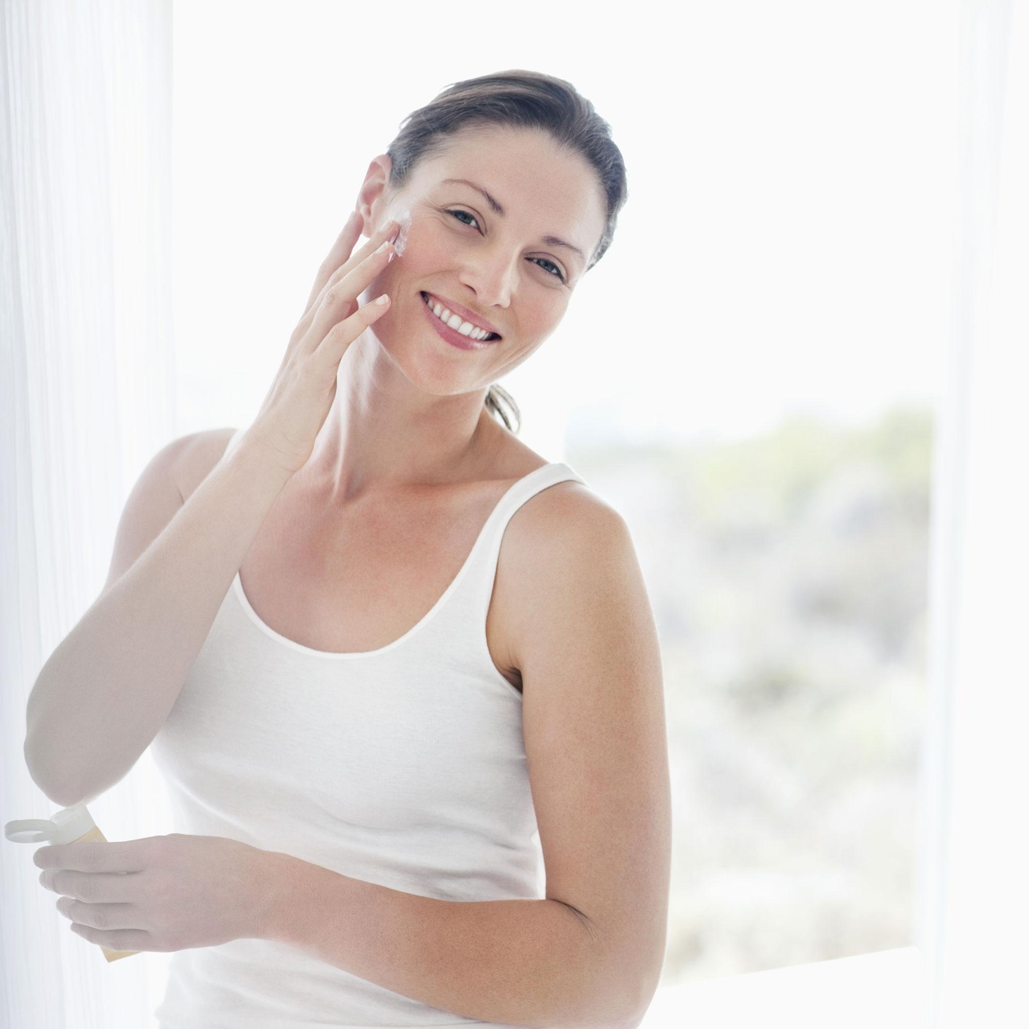 woman applying moisturiser photo
