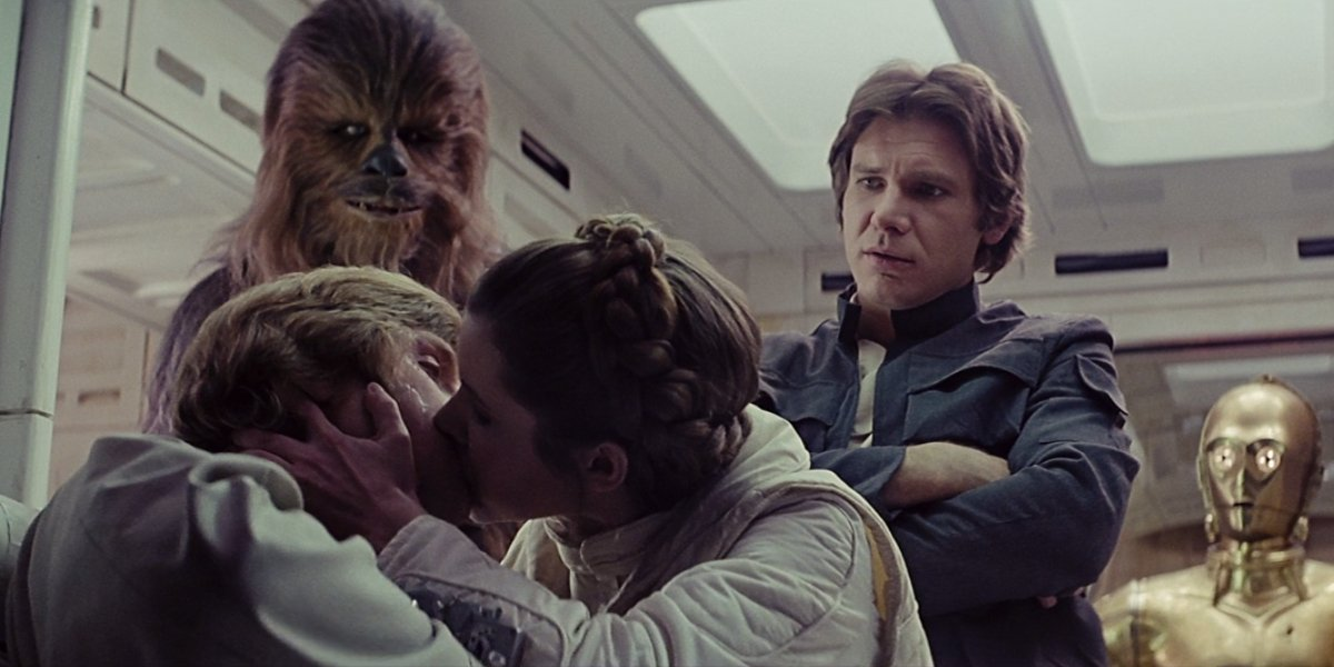Chewie, Han Solo, and C-3PO watch Luke and Leia kiss in The Empire Strikes Back.