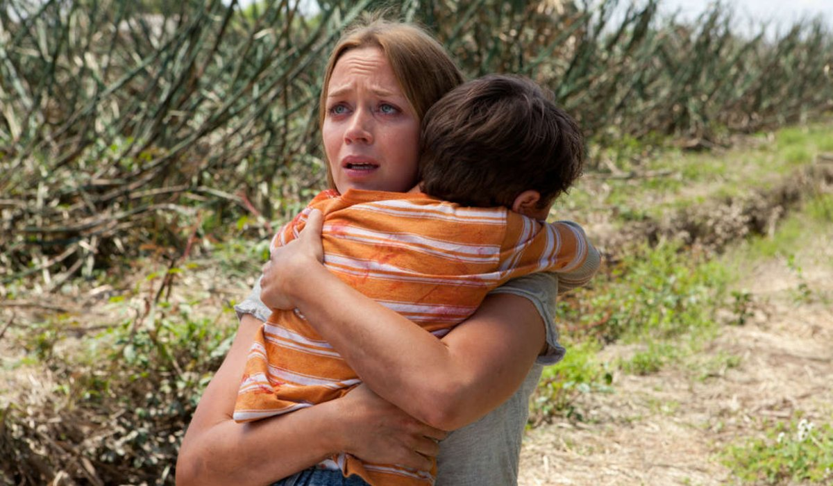 Looper Emily Blunt holds Pierce Gagnon in her arms in the field