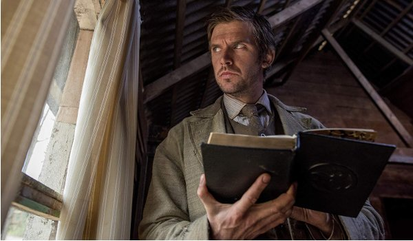 Apostle Dan Stevens flips through a book, looking out the window