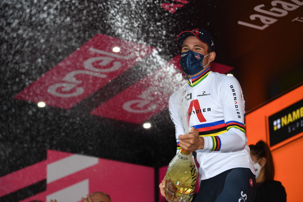 VALDOBBIADENE ITALY OCTOBER 17 Podium Filippo Ganna of Italy and Team INEOS Grenadiers World Champion Jersey Celebration Champagne Mask Covid safety measures during the 103rd Giro dItalia 2020 Stage 14 a 341km individual Time Trial from Conegliano to Valdobbiadene 254m ITT girodiitalia Giro on October 17 2020 in Valdobbiadene Italy Photo by Tim de WaeleGetty Images