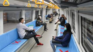 People sit on designated areas to ensure social distancing inside a light rapid transit train in Palembang, Indonesia, on March 20, 2020, amid concerns of the COVID-19 pandemic.