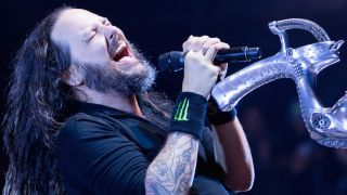 Korn's Jonathan Davis leaning back form his mic stand and singing with his eyes closed.